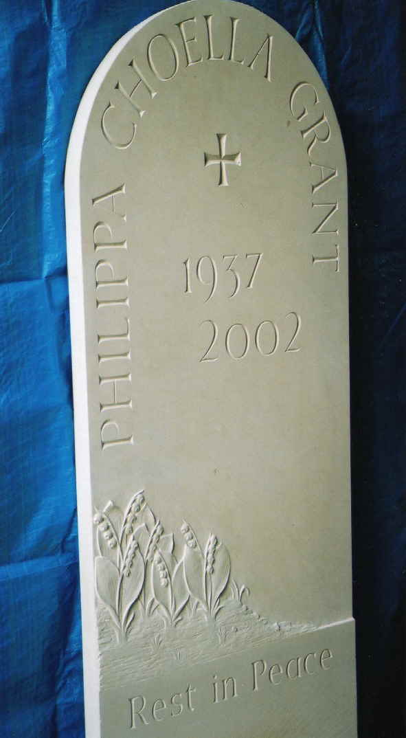 Rounded top headstone in portland stone with lilies in relief